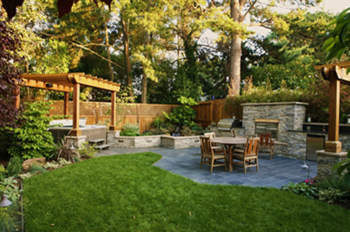 This backyard renovation created an outdoor entertainment area for cooking. The owners also wanted a large stone patio, spa, trellis, lawn area and garden.